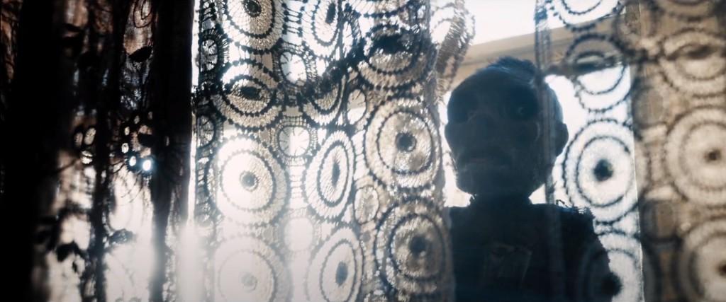 """Imágenes de """"Hechizo vudú"""" (2021). Tu omnipresente muñeco vudú te observa constantemente desde la ventana, entre los visillos"""